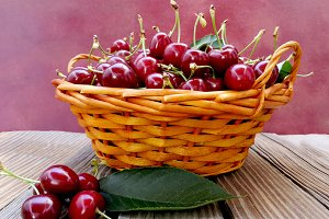 Basket of cherries on old wooden