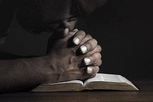 Man praying to God on a Bible