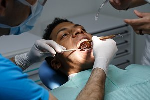 Doctor checking teeth of black man