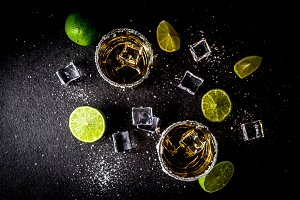 Two tequila shot glasses on dark bac