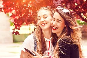 two girlfriends hug with a smile on