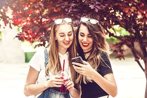two girls are looking at the phone s