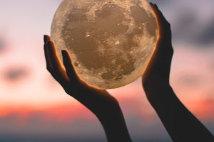 Holding the moon at sunset