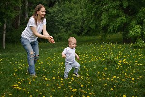 Mom and son are walking in meadow.