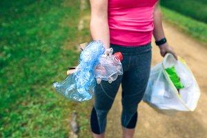 Plogging. Girl showing garbage