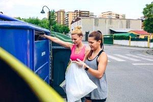 Girls throwing garbage to recycling