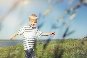 Blond boy joyful and running on natu