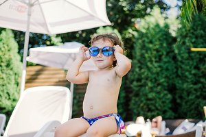 little girl in the sun by the pool