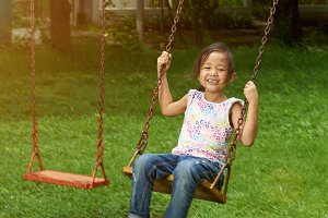 Little asian girl swing in park