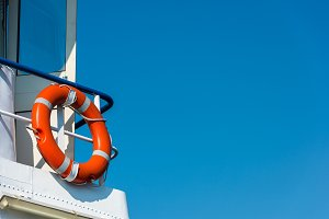 Orange lifebuoy on a white yacht