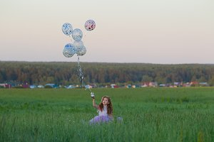 Little girl with balloons on a walk