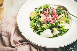 Fresh green summer salad over wooden