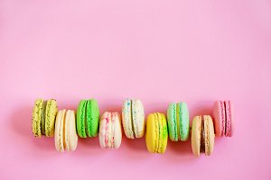 Row of colorful macarons on pink