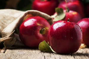 Red autumn apples with drops on rust