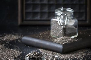 Chia seeds in small glass jar, gray