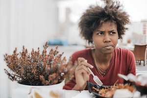 Portrait of black girl tasting salad