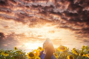 Happy woman enjoys with sunflowers