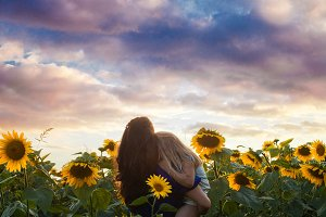 Mom and daughter among sunflowers
