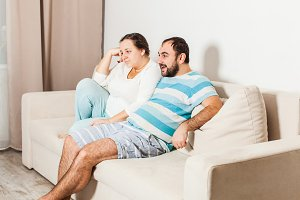 Couple at home relaxing in sofa.
