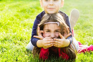 Little girl and boy playing outdoors