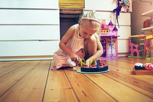 Girl slicing toy cake on the floor
