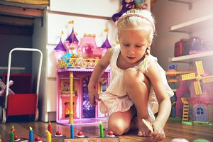 Cute little girl with sliced toy cak