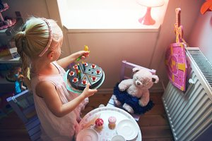 Girl holding toy cake while playing