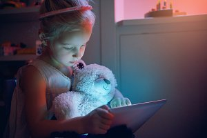 Little child browsing tablet with to