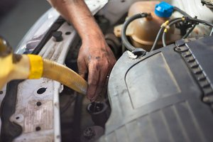 Car mechanic changing engine oil in