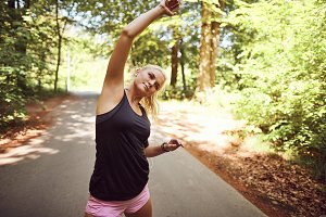 Fit woman warming up for a run in th