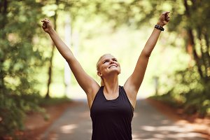 Smiling woman raising her arms in vi