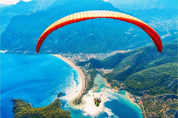 Sports Stock Photos - Paraglider tandem flying over sea