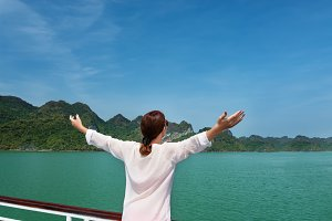 woman traveling by boat with arms up