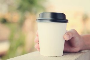 Hand holding take away coffee cup