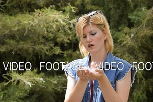 A blond woman blowing a poplar fluff