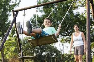 Mother swinging her son on a swing