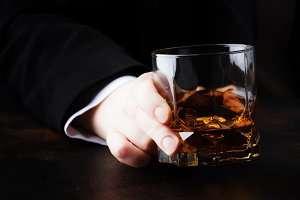 Glass with whiskey in hand, dark bac