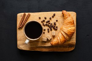 Coffee and croissant on wooden board