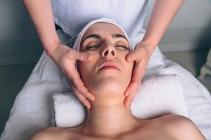Woman receiving facial treatment on