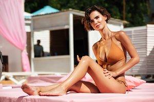 Beautiful girl in bikini sitting on