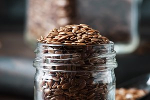 Flax seeds in glass jar, brown backg
