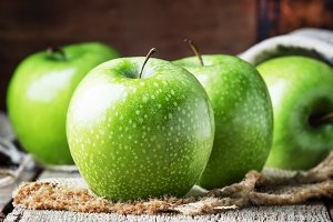 Green apples on vintage wooden backg