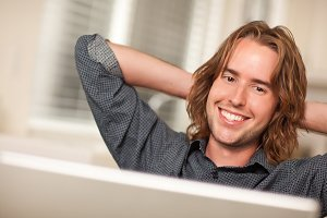 Happy Young Man Using Laptop Compute