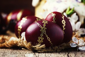 Dark red Easter eggs with a gold pat