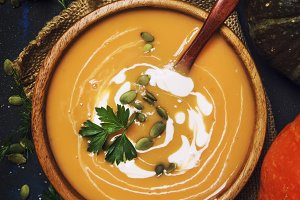Creamy pumpkin soup in wooden bowl,