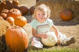 Adorable Baby Girl Holding a Pumpkin