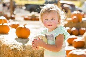 Adorable Baby Girl Holding a Pumpkin