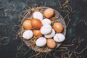 Multicolored chicken eggs with straw
