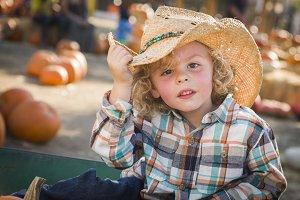 Little Boy in Cowboy Hat at Pumpkin