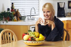 Woman with Cup of Coffee in Kitchen